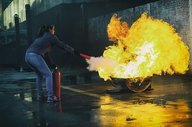 A woman using fire extinguisher trying to kill the fire