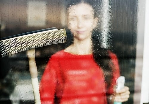 A woman wearing red blouse cleaning the window