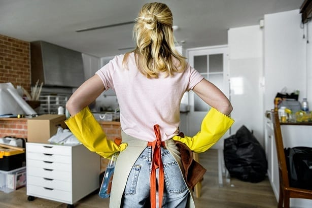 a woman wearing a yellow gloves clearing clutter around her home