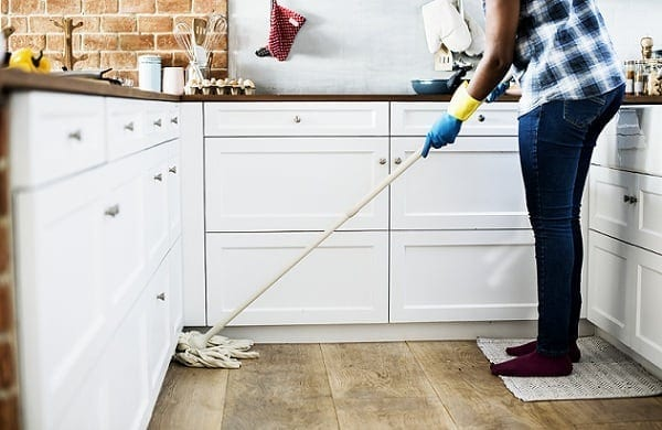 a woman who clean the dust on the floor using mop