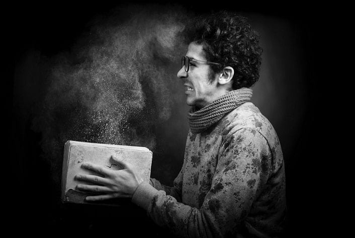 A man holding a book filled of dust
