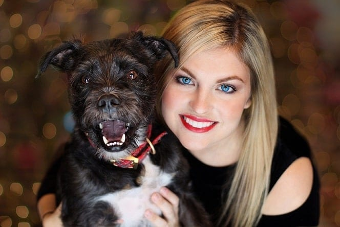 a smiling woman with her black dog