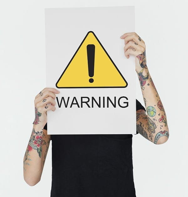 A person with tattoos on his arms and covers his face with a warning sign card