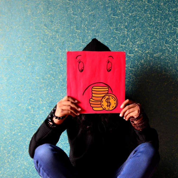 a person wearing black shirt holding a red card that covers her face which relates to increase energy bills