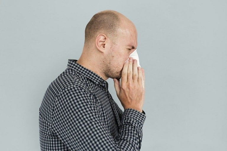 a man wearing printed black polo shirt who sneeze